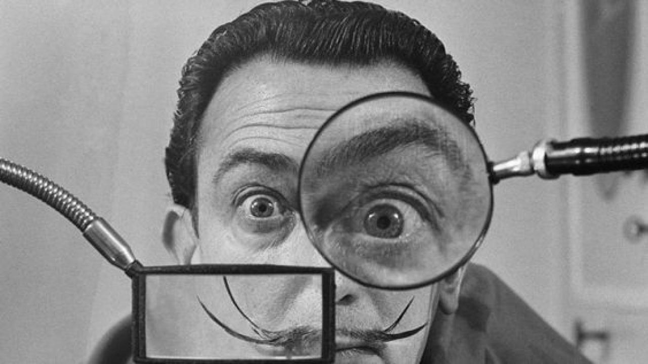 Salvador Dali looking through a magnifying glass